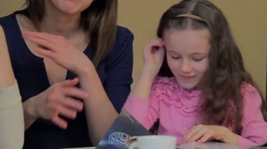 Two women with a little girl in cafe — Vídeo Stock