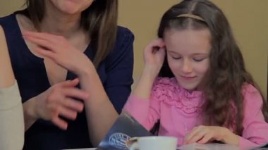 Two women with a little girl in cafe — Stok video