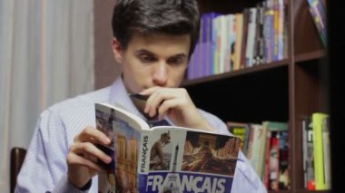 Male student learning French in library — Vídeo Stock