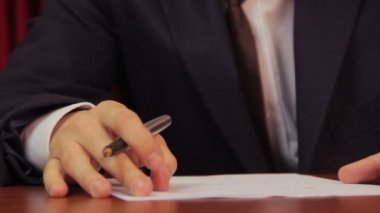 Male boss putting his signature on papers — Stock Video