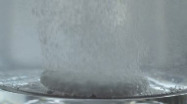 Half effervescent dose tablet dissolving in water glass — Stock Video