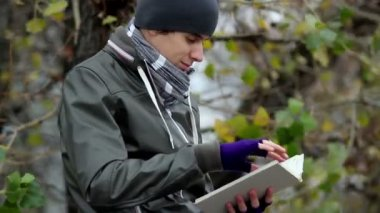 Guy reads interesting book in park — Vídeo de stock