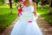 Bride with a sign. Wedding background — Stock Photo