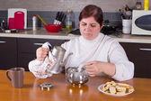 Medelålders kvinna att göra te i köket — Stockfoto