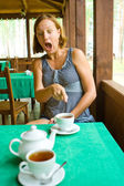 Shocked girl sees something in cup of tea — Stock Photo