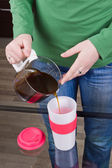 Sleepy girl pouring coffee in cup — Stock Photo