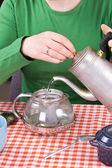 Young girl making tea at kitchen — Stock Photo
