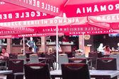 People relaxing under red umbrellas at Ursus Breweries restauran — Stock Photo