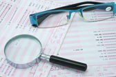 Magnifier and spectacles on bank account — Stock Photo