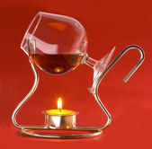 Glass with cognac and candles — Stock Photo