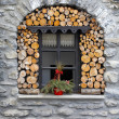 Stock Photo: Window in stone house with woodpile