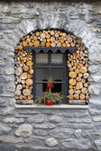 Window in the stone house with woodpile — Stock Photo
