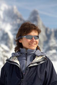 The girl in glasses on a background of snow mountains — Stock Photo