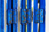 Wooden door with blue hinge — Stock Photo