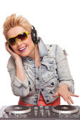 Attractive beautiful DJ girl with headphones at dj mixer playing isolated on white — 图库照片