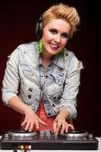Attractive beautiful DJ girl with headphones at dj mixer playing — Stock Photo