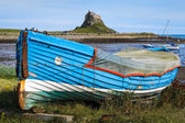 Old rowing boat and a view of Holy Isalnd Lindisfarne — Stock Photo