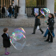Stock Photo: Young girl closely examining two very large bubbles