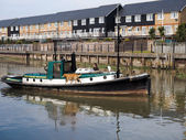 Small tug towing Cambria Thames sailing barge in Faversham Kent on March 29, 2014. Unidentified man. — Stock Photo
