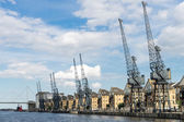 Old dockside cranes alongside a waterfront development — Stock Photo