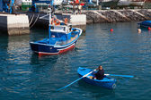 Man rowing a fishing boat to side of harbour in Tenerife — Stock Photo