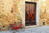 Red bicycle leaning against a wall in Pienza — Stock Photo