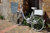 White bicycle leaning against a wall in Pienza Tuscany — Stock Photo