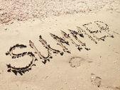 Verão de palavra na areia da praia — Fotografia Stock
