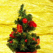 Little decorated christmas tree on golden background with gifts — Stock Photo