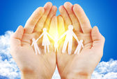 Paper family in hand sun and blue sky — Stock Photo
