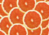 Fresh grapefruit and slices background — Stock Photo