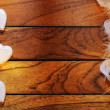 Stock Photo: Three white hearts misaligned and feathers