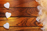 Three white hearts misaligned and feathers — Stock Photo