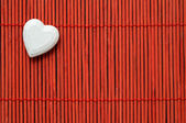 Heart on red bamboo top left corner — Stock Photo