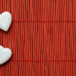 Stock Photo: Two hearts on red bamboo lined