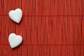 Two hearts on red bamboo lined — Stock Photo