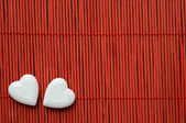 Two hearts on red bamboo — Stock Photo