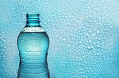 Aqua bottle on background with drops — Стоковое фото