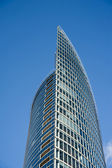 Modern business glass building on blue sky background — Стоковое фото