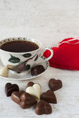 Tea cup with heart shaped chocolates — Stock Photo