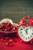 Valentine heart shaped red love clock with chocolates — Stock Photo