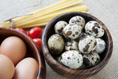 Dry pasta, tomatoes and eggs in wooden bowls on sack background — Stock Photo