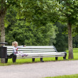 Little blonde girl sitting on the bench in the park — Stock Photo