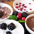 Sweet cream dessert with chocolate and berries in white porcelai — Stock Photo