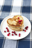 Heart shaped pancakes with cranberries on porcelain plate. Closeup — Стоковое фото