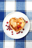 Love heart pancakes with cranberries on porcelain plate. Closeup — Stock Photo