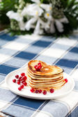 Heart shaped pancakes with cranberries on porcelain plate. Close — Стоковое фото
