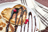 Heart shaped pancakes with chocolate sauce and cranberries. — Stock fotografie