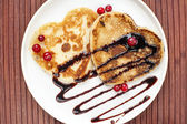 Heart shaped pancakes with chocolate sauce and cranberries. — Стоковое фото