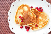 Heart shaped pancakes with cranberries on porcelain plate. Close — Zdjęcie stockowe